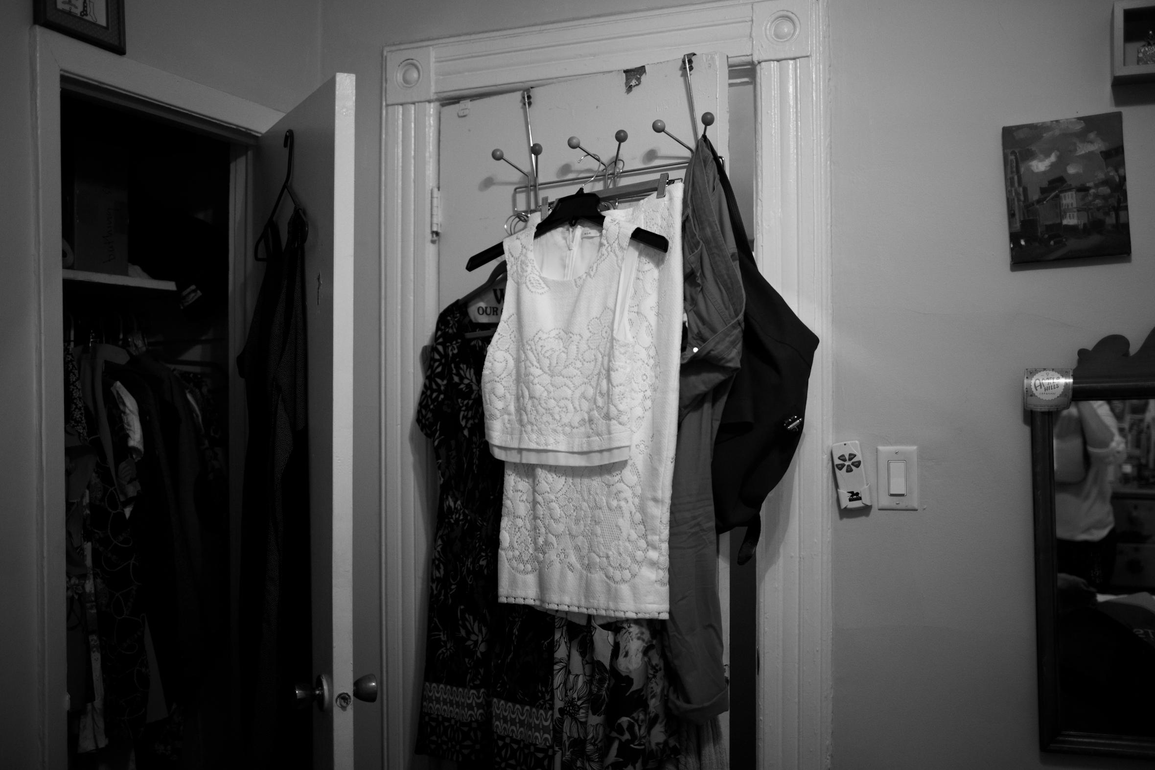two piece white wedding dress hanging on door